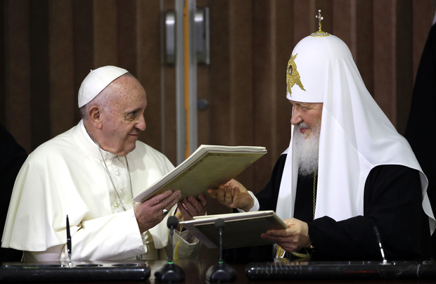 Pope Francis (L) and the head of the Russian Orthodox Church, Patriarch Kirill exchange documents during a historic meeting in Havana on February 12, 2016. Pope Francis and Russian Orthodox Patriarch Kirill kissed each other and sat down together Friday at Havana airport for the first meeting between their two branches of the church in nearly a thousand years. AFP PHOTO / POOL - Gregorio Borgia / AFP / POOL / GREGORIO BORGIA