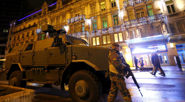 A Belgian soldier patrols near an armoured vehicle in central Brussels after security was tightened in Belgium following the fatal attacks in Paris.