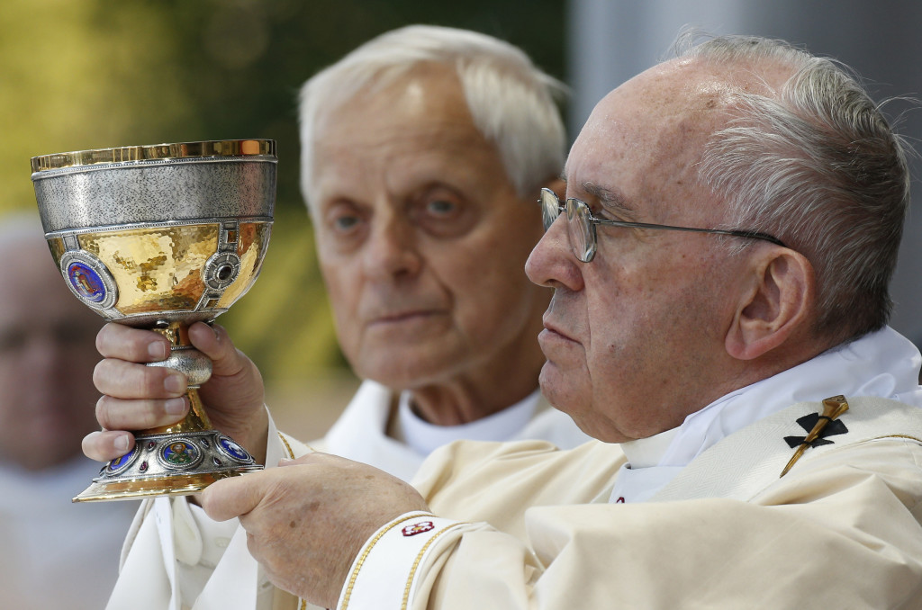 Pope Francis raises chalice as he celebrates Mass outside the Basilica of the National Shrine of the Immaculate Conception in Washington